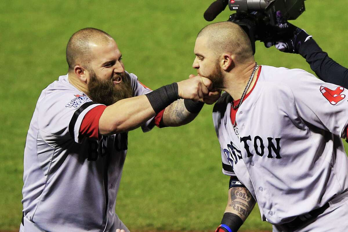 Mike Napoli of the Boston Red Sox yanks the beard of teammate Jonny Gomes after hitting a three-run home run against the St. Louis Cardinals in Game Four of the World Series. One of our readers finds the facial hair a bit distracting.