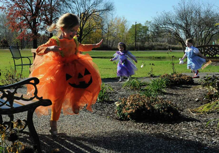 From left, Grace Kelly-Salisbury, 5, of Latham Ella Dowling, 4, of Loudonville and Molly McMillen, 3, of Voorheesville  run around the garden area of the The William K. Sanford Town Library after a Halloween parade in the library on Tuesday, Oct. 29, 2013 in Colonie, N.Y. (Lori Van Buren / Times Union) Photo: Lori Van Buren