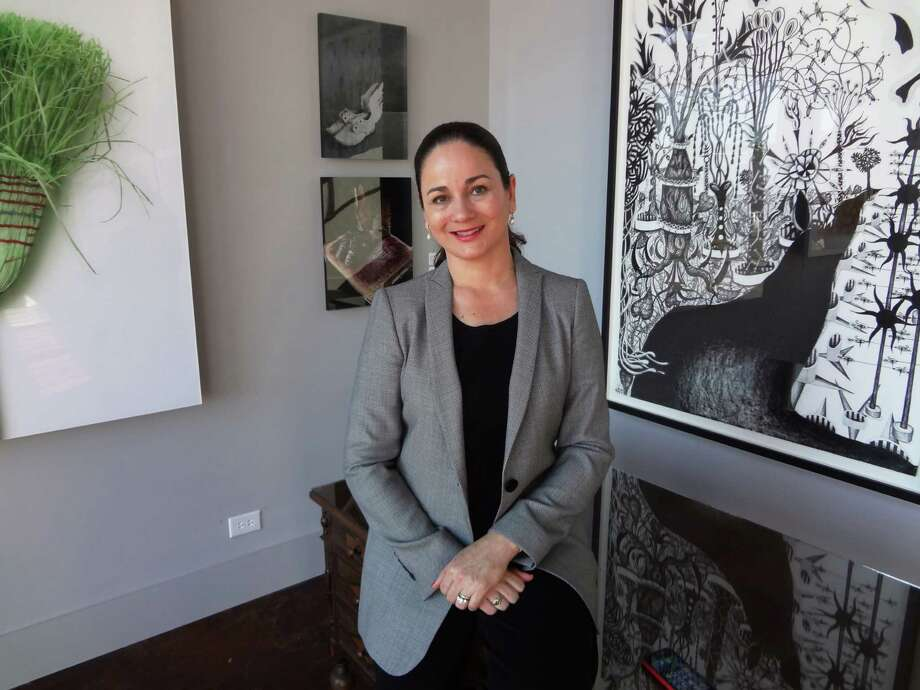 Patricia Ruiz-Healy, who has shown the work of  artists in  private exhibitions in her home, has opened a  gallery, Ruiz-Healy Art, just off Olmos Circle. Behind her are works by Chuck Ramirez (from left), Cecilia Paredes and Nicolas Leiva. Photo: Steve Bennett / San Antonio Express-News