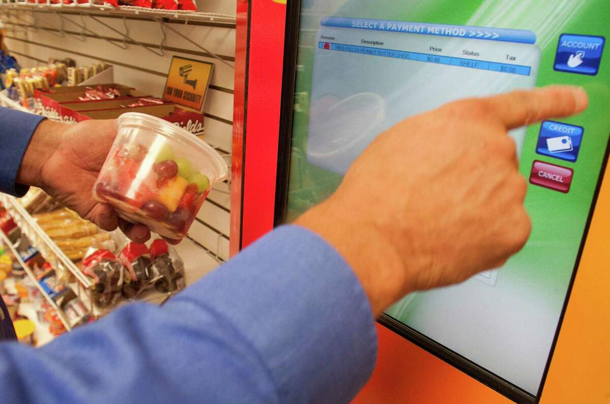 Chuck Olson of CNC Vending uses an electronic checkout at Grocers Supply. CNC provides self-checkout kiosks at an increasing number of companies.