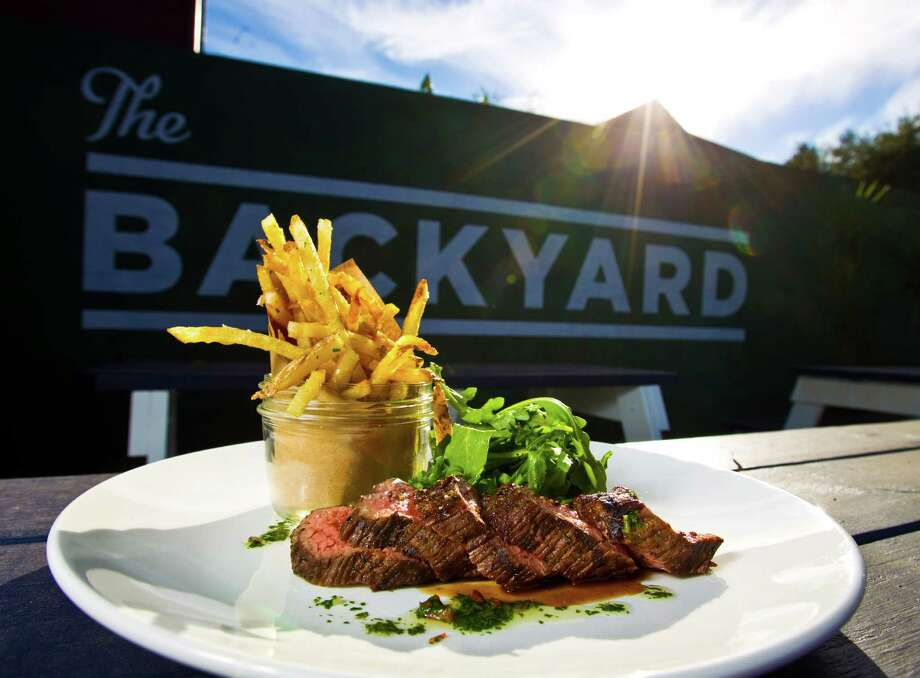 The Brooklyn Athletic Club's grilled sirloin beef, baby arugula, hand-cut fries and chimichurri. Diners can have a seat indoors or out, where croquet and bocce ball await. Photo: Nick De La Torre, Staff / © 2012  Houston Chronicle
