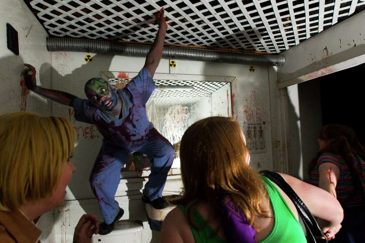 A zombie frightens guest as they walk through Scream World on Sunday, Oct. 27, 2013, in Houston. ( J. Patric Schneider / For the Chronicle )