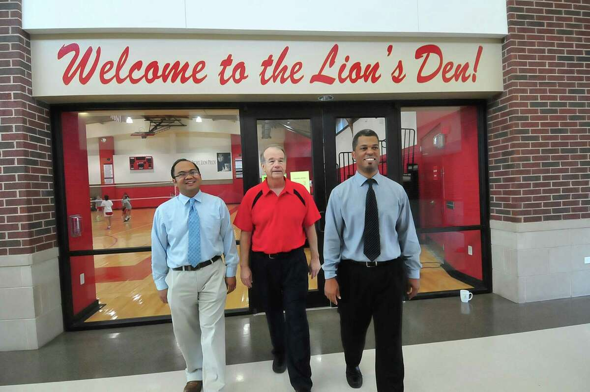 Roland Millare, left, Don Lupton and Jerome Llorens walk in the gym and Crosthwait Student Center, the newest additions at Pope John XXIII High School. They have all been at the school since it opened 10 years ago. Millare teaches theology, Lupton, social studies and Llorens, math.