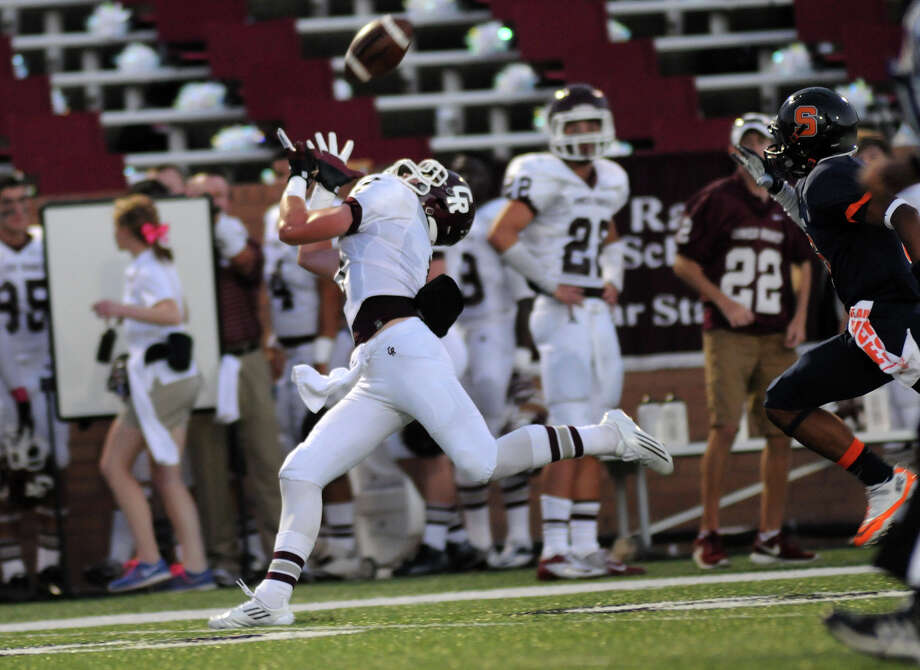 Cinco Ranch senior wide receiver Geryn Young makes a catch in front of Seven Lakes senior defensive back Nicholas Mika late in the second quarter of their district matchup at Rhodes Stadium in Katy last week. Photo: Jerry Baker, Freelance