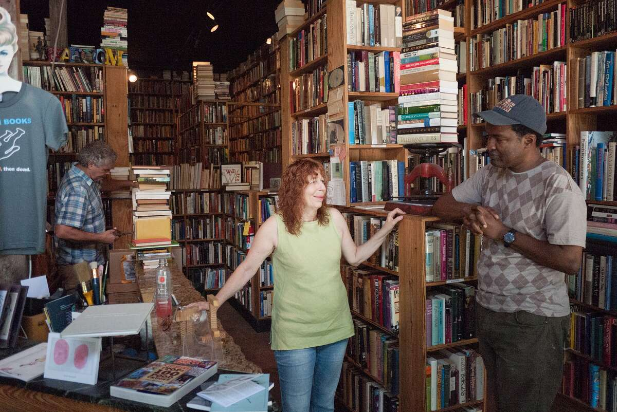 Kaboom Books co-owner John Dillman, left, checks a newly acquired book as wife and co-owner Dee Dillman talks with customer Darin Forehand.