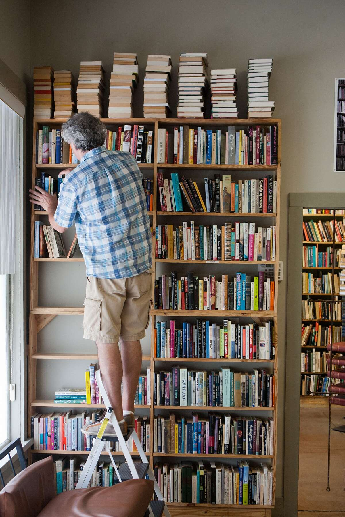 John Dillman rearranges a shelf at Kaboom Books to make space for piles of books for shoppers to browse.
