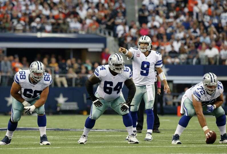 Dallas Cowboys quarterback Tony Romo (9) signals from the line of scrimmage as Doug Free (68), Brian