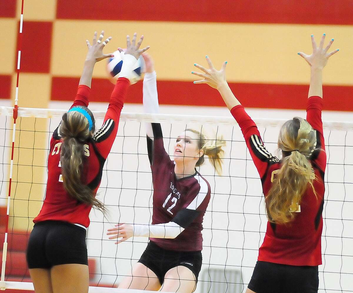Cy-Fair's Keely Hayes, center, slipped a kill past two Cy Woods defenders in the Bobcats' win last week.