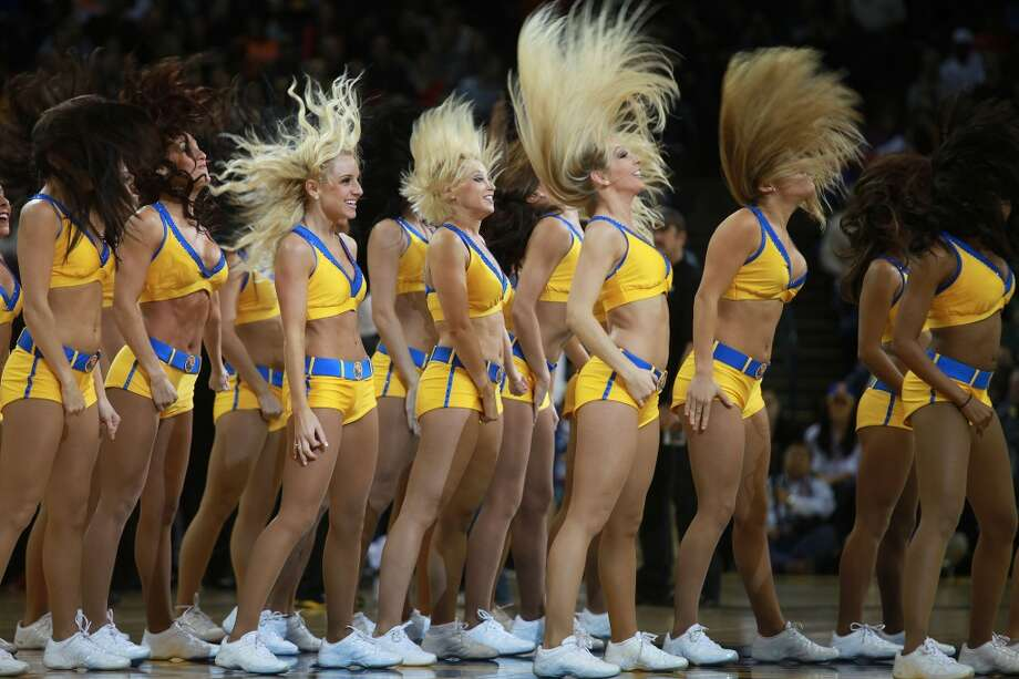 Hair flip - 9:00p.m. - Oracle Arena.  The Warrior girls rev up the fans during a timeout as the Warriors played the Miami Heat. The classic hair flip during one of their dance routines made an interesting shot.  Camera settings: Canon 5D MkII,  ISO 800, 1/2400, f3.5,  200mm. Photo: Liz Hafalia, The Chronicle
