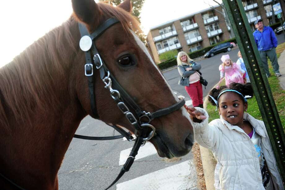 Five-year-old Milan Cannon pets the police escort horse Tuesday, Oct. 29, 2013 during the 5th Annual Black Rock Halloween Parade & Block Party beginning at Ellsworth Park and ending at the Black Rock Branch Library. Photo: Autumn Driscoll / Connecticut Post