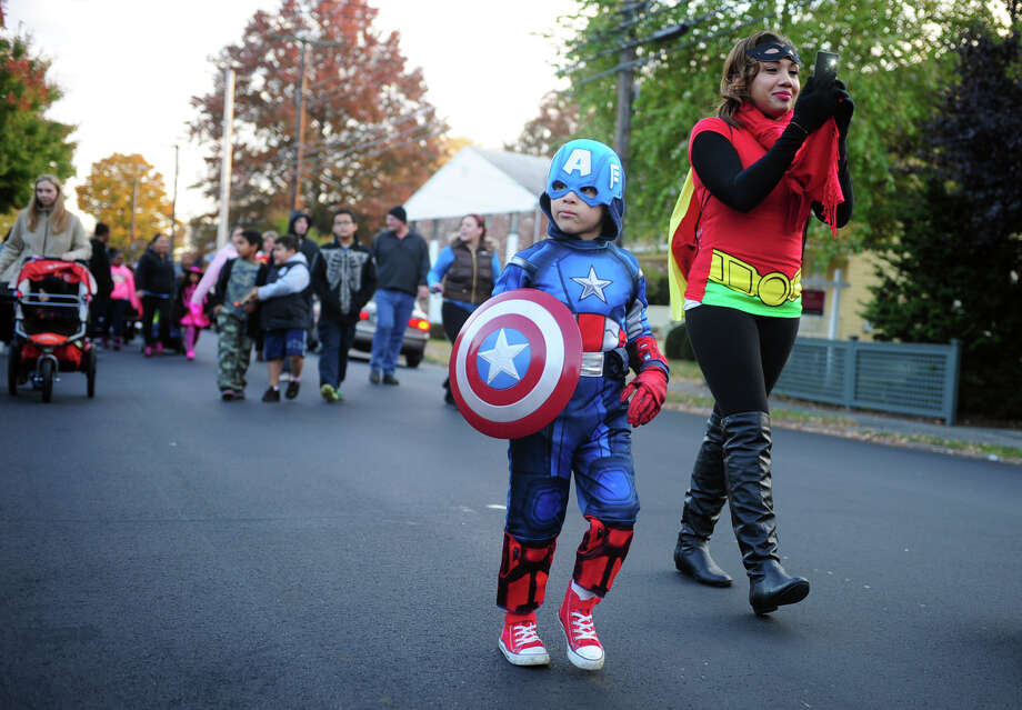Superheroes Jaiden Hoffman, 5, and Erika Culley, of Bridgeport, walk up Ellsworth Street Tuesday, Oct. 29, 2013 during the 5th Annual Black Rock Halloween Parade & Block Party beginning at Ellsworth Park and ending at the Black Rock Branch Library. Photo: Autumn Driscoll / Connecticut Post