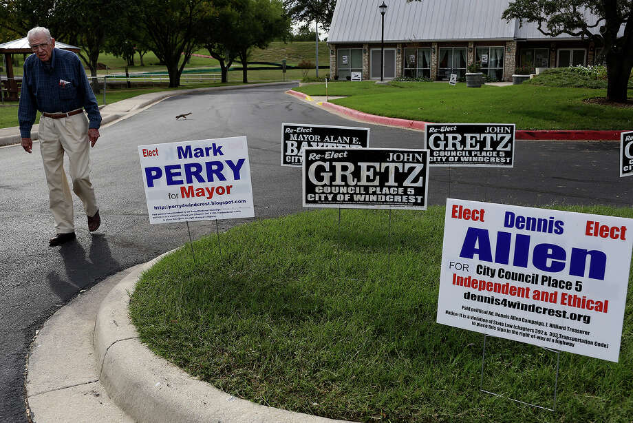 James Calhoun walks by campaign signs for opposing candidates outside the early voting site at Takas Park Civic Center in Windcrest on Tuesday, Oct. 29, 2013. Photo: Lisa Krantz, San Antonio Express-News / San Antonio Express-News