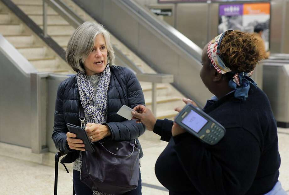 Rockridge BART Station agent Collette Brown (right) helps passenger Karen Stevenson, who ran out of fare. BART's Addfare kiosks only take cash, leaving those without out of luck. Photo: Carlos Avila Gonzalez, The Chronicle