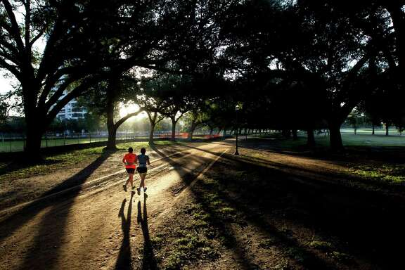 Runners jog along the Marvin Taylor Trail in Hermann Park at sunrise Tuesday, Oct. 29, 2013, in Houston.