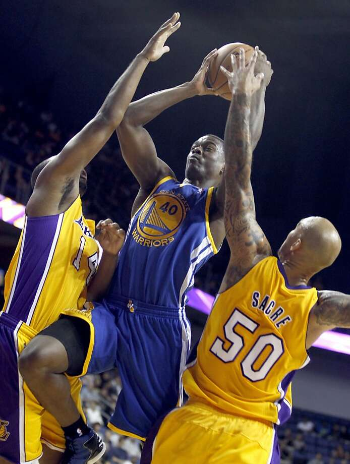 Golden State Warriors forward Harrison Barnes, center, splits the defense of Los Angeles Lakers forward Marcus Landry, left, and Lakers center Robert Sacre (50) in the fourth quarter during an NBA basketball preseason game Saturday, Oct. 5, 2013, in Ontario, Calif. Lakers won the game 104-95.   (AP Photo/Alex Gallardo) Photo: Alex Gallardo, Associated Press