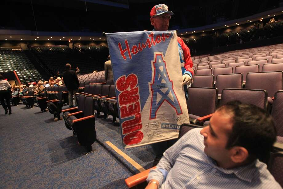 An Oilers fan shows a piece of memorabilia at the memorial ceremony for Bum Phillips. Photo: Mayra Beltran, Houston Chronicle