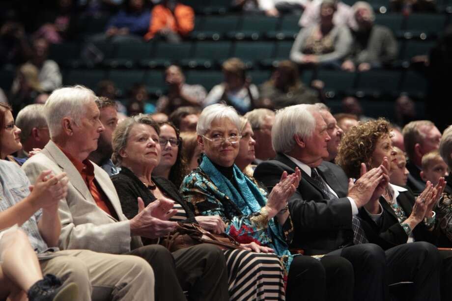 Debbie Phillips claps along to the 'Luv Ya Blue' song during the memorial service for her deceased husband Bum. Photo: James Nielsen, Houston Chronicle