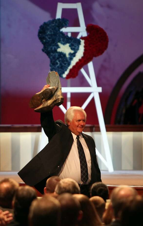 "Wade Phillips holds up boots presented to him by Carl Mauck during the memorial service for his father Oail Andrew ""Bum"" Phillips. Photo: Mayra Beltran, Houston Chronicle"