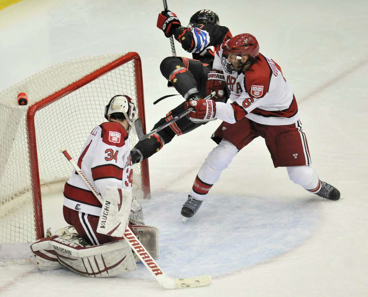 Rensselaer Polytechnic Institute's Johnny Rogic, center, puts the puck past Harvard University goalie Steve Michalek (34) while being defended by Kevin Guiltinan (6) during the first period of a ECAC college hockey game in Troy N.Y., Tuesday, Oct. 29, 2013. (Hans Pennink / Special to the Times Union) ORG XMIT: HP101