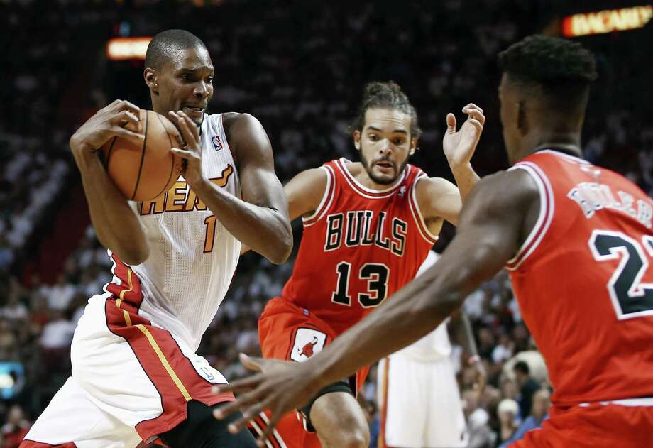 Miami Heat's Chris Bosh (1) tries to drive between Chicago Bulls' Joakim Noah (13) and Jimmy Butler (22) during the first half of an NBA basketball game in Miami, Tuesday, Oct. 29, 2013. (AP Photo/J Pat Carter) ORG XMIT: FLJC101 Photo: J Pat Carter / AP