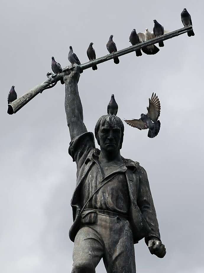 Pigeons roost under grey skies on the statue of Benjamin Rush Milam in Milam Park, Tuesday, Oct. 29, 2013, in downtown San Antonio. Thunderstorms and rain showers likely for South Texas Wednesday. (AP Photo/Eric Gay) Photo: Eric Gay, Associated Press