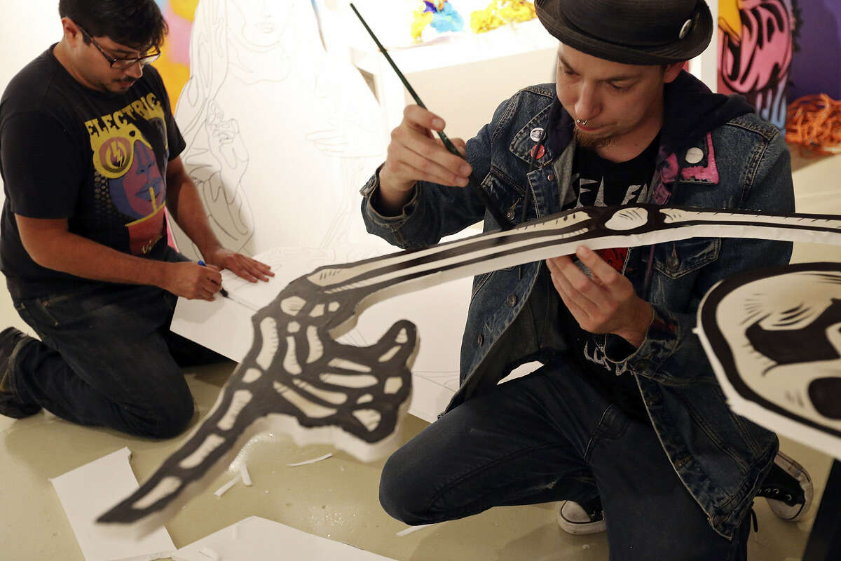 """Louie Chavez (left) and David """"Shek"""" Vega work on their altar, which honors numerous people."""