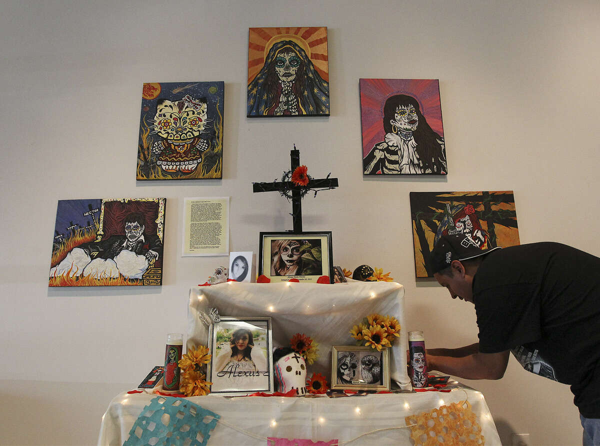 Artist Israel Rico makes adjustments to an altar in tribute to his girlfriend's daughter at Centro Cultural Aztlan.