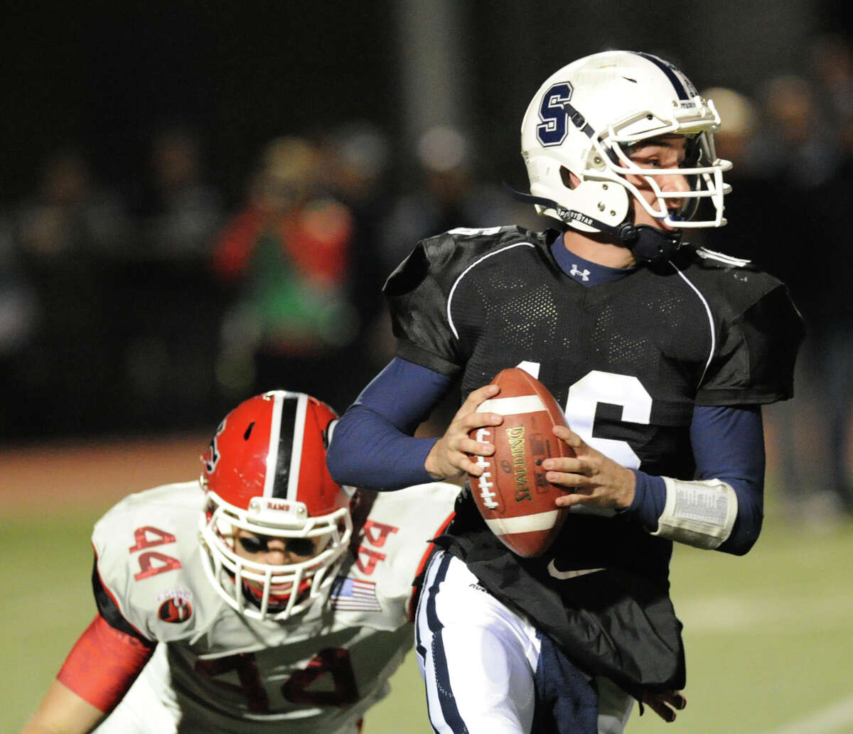 Staples quarterback Jack Massie (# 16), at right, is pursued by Zachary Allen (# 44) of New Canaan during the high School football game between Staples High School and New Canaan High School at Staples in Westport, Friday night, Oct. 25, 2013.