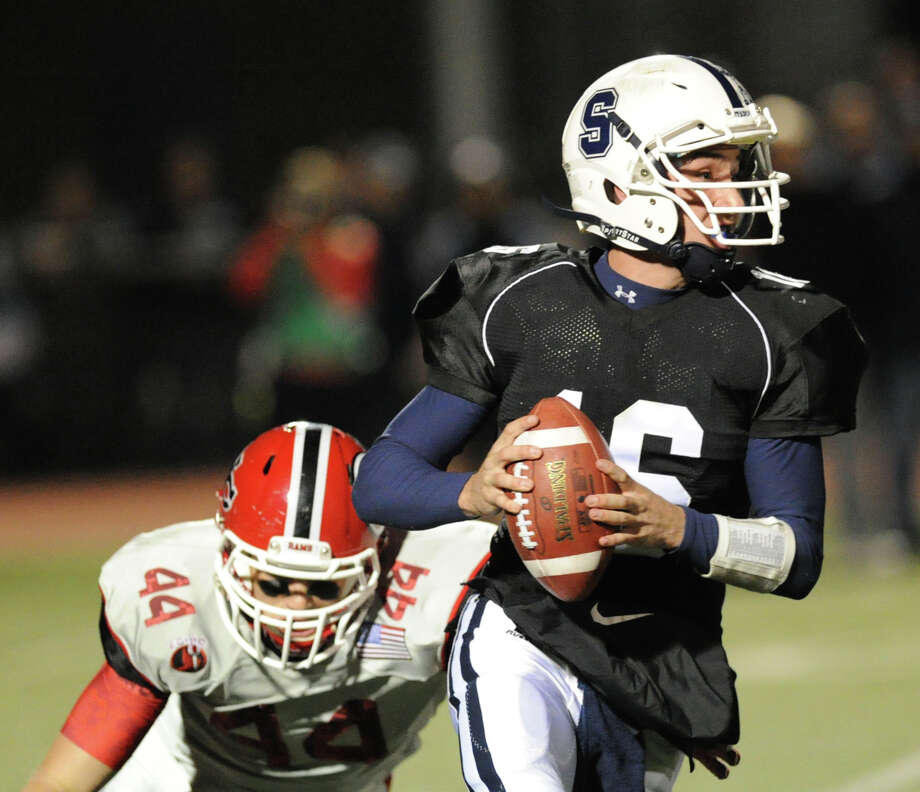 Staples quarterback Jack Massie (# 16), at right, is pursued by Zachary Allen (# 44) of New Canaan during the high School football game between Staples High School and New Canaan High School at Staples in Westport, Friday night, Oct. 25, 2013. Photo: Bob Luckey / Greenwich Time
