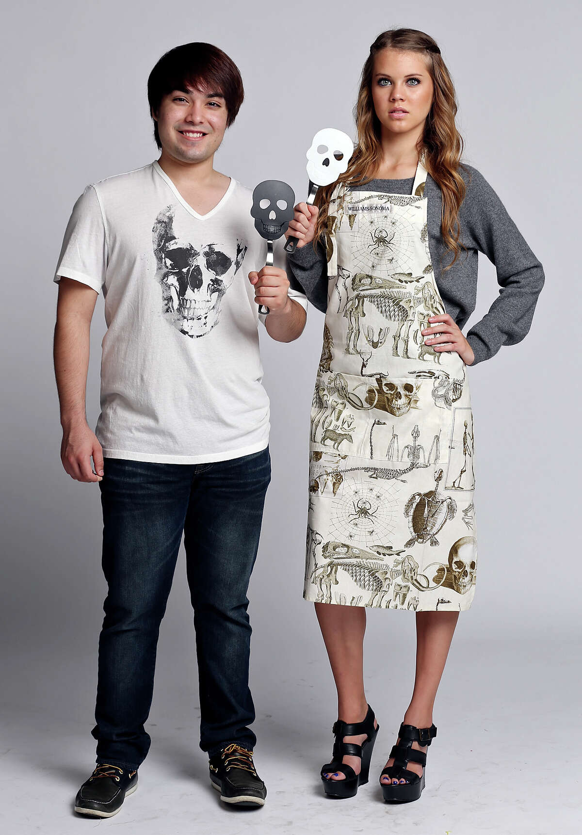 Jose Munoz (left) models a John Varvatos skull T-shirt, $69, Neiman Marcus and Kassi Pena models a cashmere skull sweater by 360 Cashmere, $298, Neiman Marcus and Skellie Toile apron, $29.99, from Williams Sonoma. Both hold skull spatulas,Williams Sonoma, $12.95.