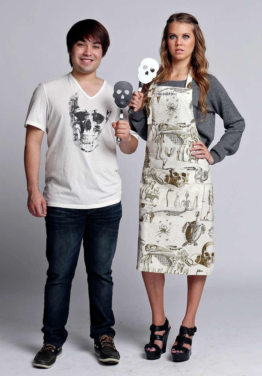 Jose Munoz (left) models a John Varvatos skull T-shirt, $69, Neiman Marcus and Kassi Pena models a cashmere skull sweater by 360 Cashmere, $298, Neiman Marcus and Skellie Toile apron, $29.99, from Williams Sonoma. Both hold skull spatulas,Williams Sonoma, $12.95.