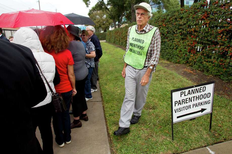 Volunteer Neal Parker keeps protestors off Planned Parenthood property during a demonstration outside the building Wednesday, Oct. 30, 2013, in Houston. The event was to protest U.S. District Judge Lee Yeakel's Oct. 28 ruling that a provision in Texas law to require abortion providers to have admitting privileges at nearby hospitals is unconstitutional. Photo: Brett Coomer, Houston Chronicle / © 2013 Houston Chronicle