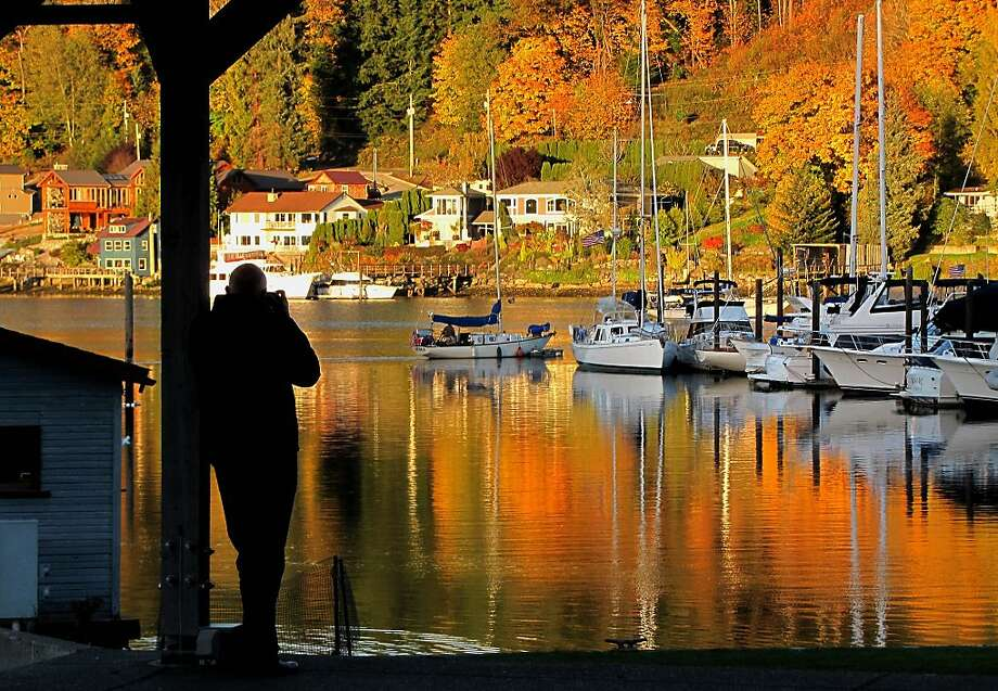 As the sun sets,Gig Harbor marina glows with fall color reflected from Skansie Brothers Park in Kitsap, 
