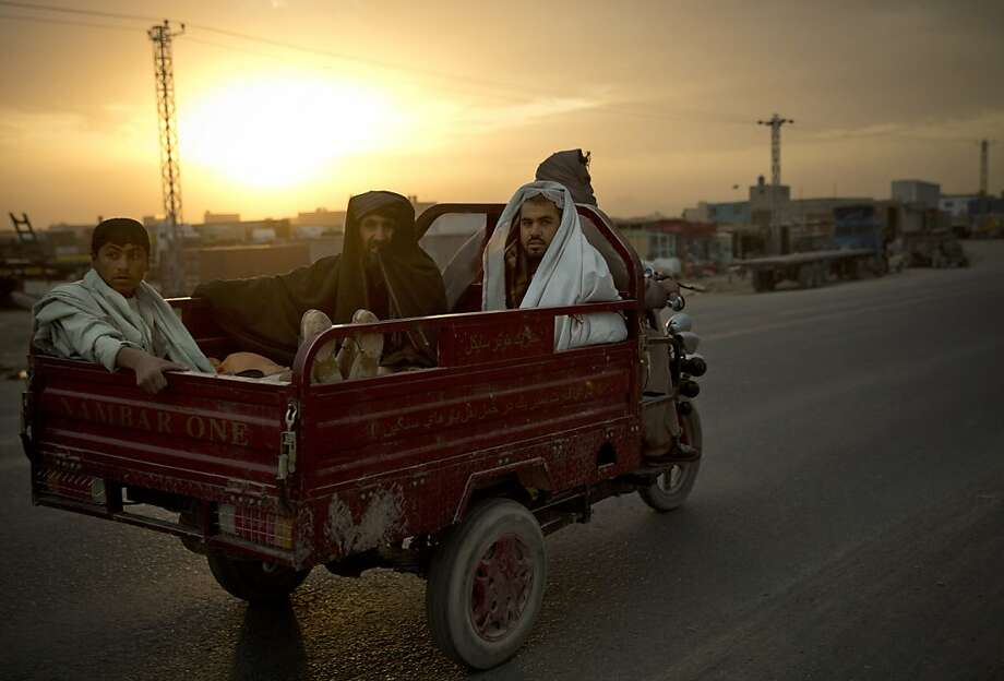Transit trike:Three Afghan men share a cab back into town on the outskirts of Kandahar. Photo: Anja Niedringhaus, Associated Press