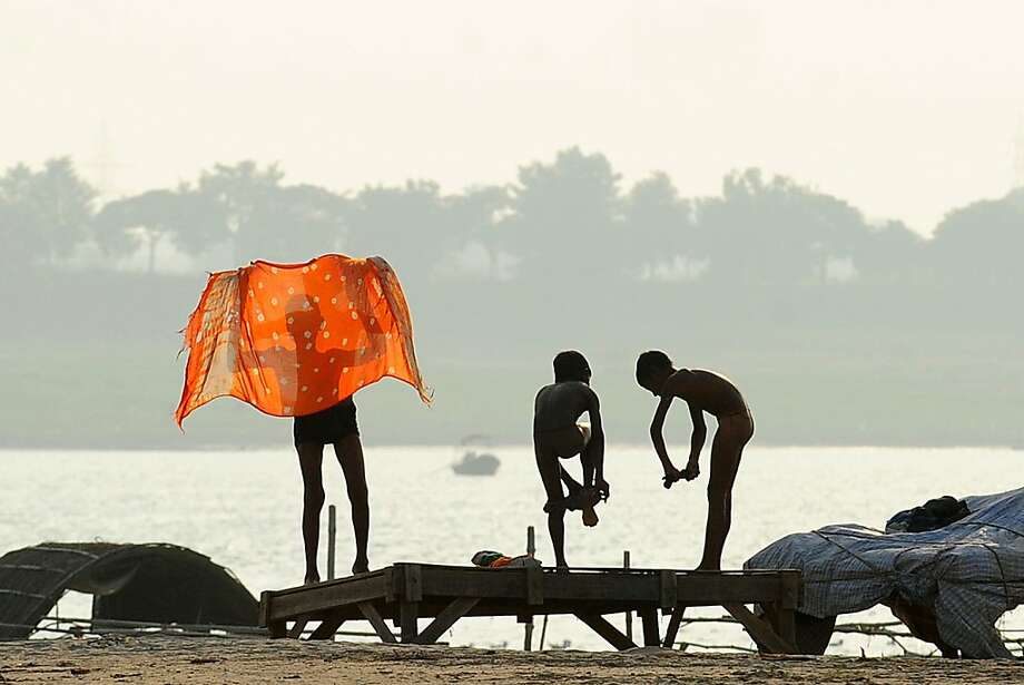 Holy skinny dip:Indian boys get dressed after swimming in the Sangam, the sacred confluence of three rivers in 