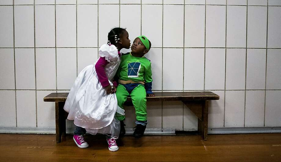 "This is just like a game that ends in a tie: Two-year-old Jordan Sims flinches as big sister Jasmine Sims tries to kiss him at Scott Elementary School's Halloween festival in Flint, Mich. ""I like my brother, and I like to give him kisses,"" Jasmine announced to all those present. Photo: Jake May, Associated Press"