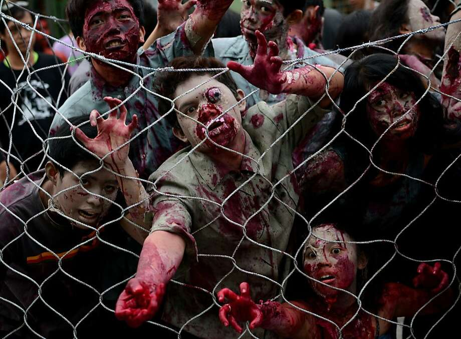 One of the things we're thankful for on this Halloween - chain-link fences. (Halloween Costume Parade in Manila.) Photo: Noel Celis, AFP/Getty Images