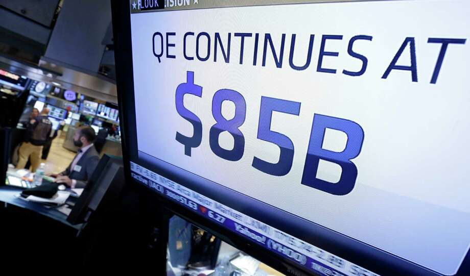 The decision of the Federal Reserve appears on a television screen on the floor of the New York Stock Exchange Wednesday, Oct. 30, 2013. The Fed says in a statement after a two-day policy meeting that it will keep buying $85 billion a month in bonds to keep long-term interest rates low and encourage more borrowing and spending.  (AP Photo/Richard Drew) ORG XMIT: NYRD116 Photo: Richard Drew / AP