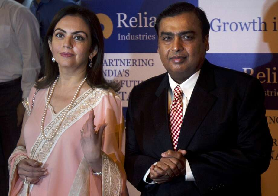 No. 38 -- Reliance Industries Chairman Mukesh Ambani, 56  Ranked No. 37 in 2012, Ambani is India's richest man, overseeing the $50 billion petrochemical conglomerate Reliance Industries.  [Photo: India's Reliance Industries chairman Mukesh Ambani (right) and his wife Nita pose for photographs as they arrive for the company's annual general meeting in Mumbai, India, Thursday, June 7, 2012.] Photo: Rafiq Maqbool, Associated Press