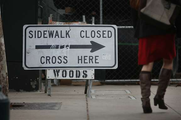 A pedestrian takes a detour from the sidewalk on the Embarcadero near the site of the proposed 8 Washington project on Tuesday, October 29, 2013 in San Francisco, Calif.