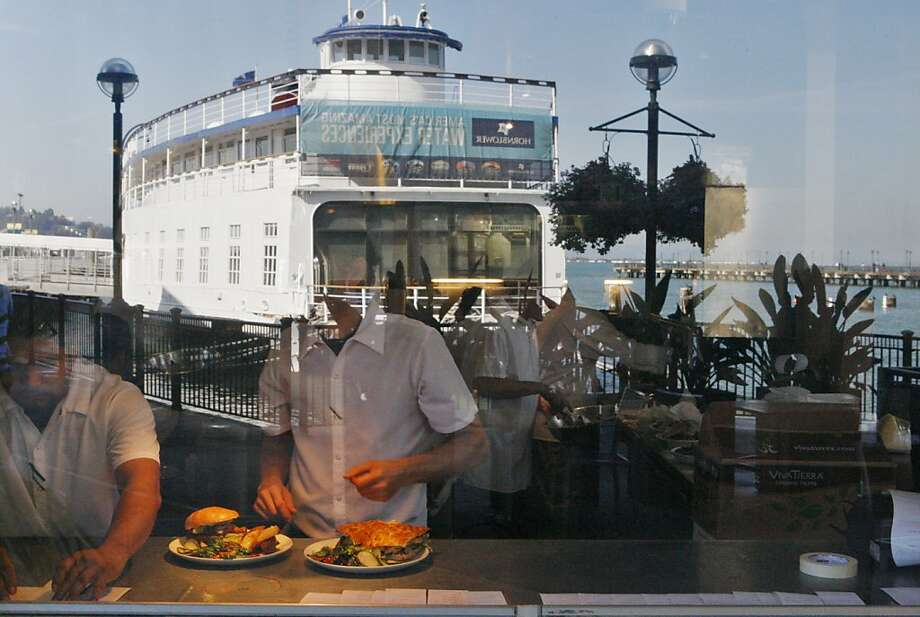 With the historic Santa Rosa Ferryboat reflected in the window, cooks prepare plates at the Plant Cafe Organic at Pier No. 3 in San Francisco. Below, diners enjoy lunch and views from the patio. Photo: Raphael Kluzniok, The Chronicle