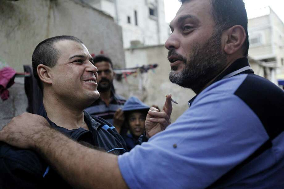 Released prisoner Omar Masoud (left), arrested in 1993 for killing an Israeli lawyer, is greeted Wednesday  in Palestinian Gaza City. Photo: Adel Hana / Associated Press