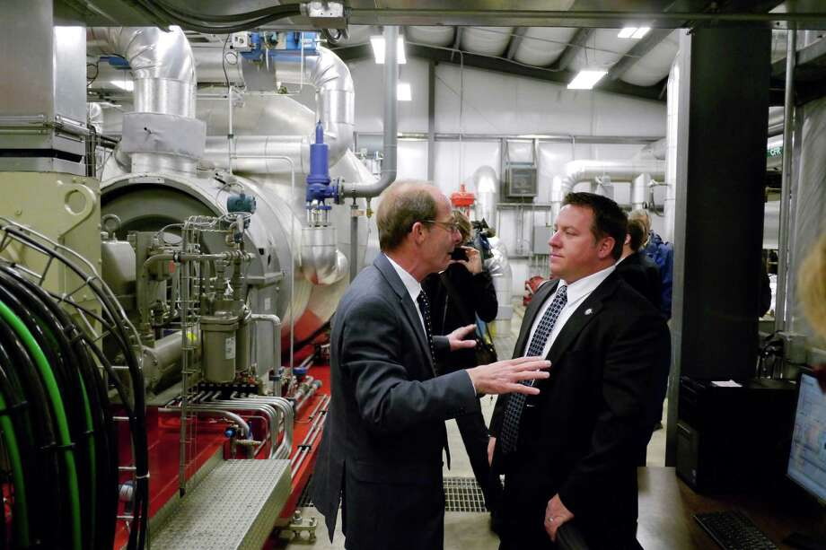 Richard Lyons, left, executive director, Sewer District, talks to Dan McCoy, Albany County Executive as he shows McCoy the new power generator plant that runs off waste heat during a press event at the North Wastewater Treatment Plant on Wednesday, Oct. 30, 2013.     The county has recently installed a combined heat and power system that captures heat created by sludge disposal.  (Paul Buckowski / Times Union) Photo: Paul Buckowski / 00024431A