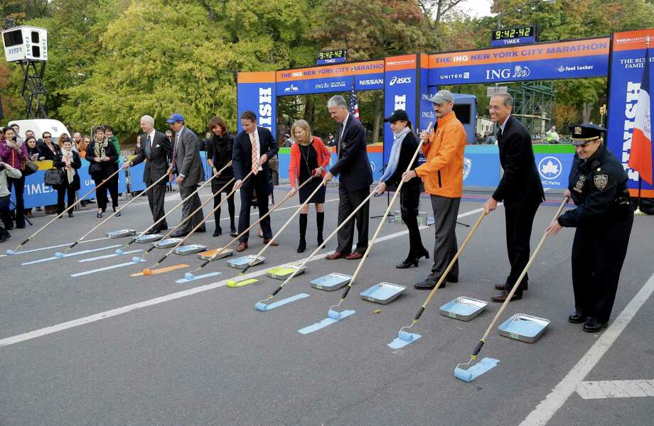 VIPs and officials, including Mary Wittenberg, New York Road Runners President and CEO, fifth from left, and Thomas Grilk, Executive Director of the Boston Athletic Association, sixth from left, participate in the ceremonial painting of the course line at the finish of the NYC Marathon in New York, Wednesday, Oct. 30, 2013. The yellow color being painted by Grilk is associated with the Boston Marathon and is being included at the NYC Marathon to honor victims and first responders of the 2013 Boston marathon bombings. The NYC Marathon is scheduled to be run on Sunday, Nov. 3, 2013. (AP Photo/Seth Wenig) ORG XMIT: NYSW104 Photo: Seth Wenig / AP