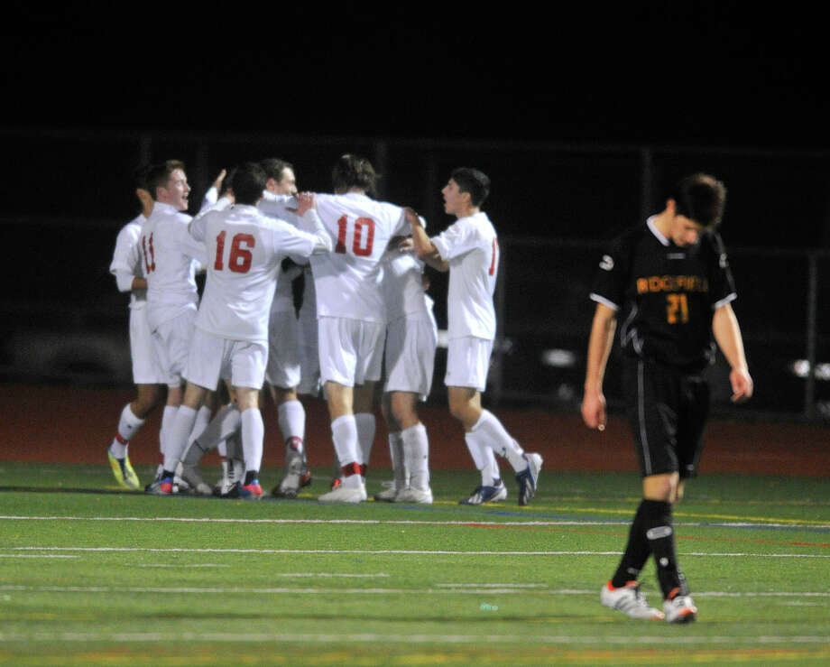 The Greenwich soccer team celebrates after scoring their fourth goal against Ridgefield during their FCIAC championship final at Norwalk High School in Norwalk, Conn., on Wednesday, Oct. 20, 2013. Greenwich won, 4-1. Photo: Jason Rearick / Stamford Advocate