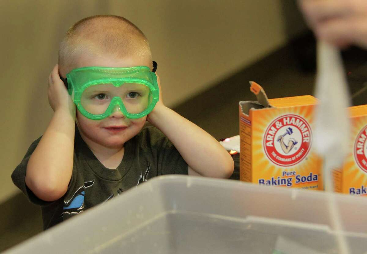 Brody Kurncz, 3, of St. Johns, MI covers his ears as a baggie explodes during an experiment at the Mad Scientist Day at MD Anderson's Proton Therapy Center.
