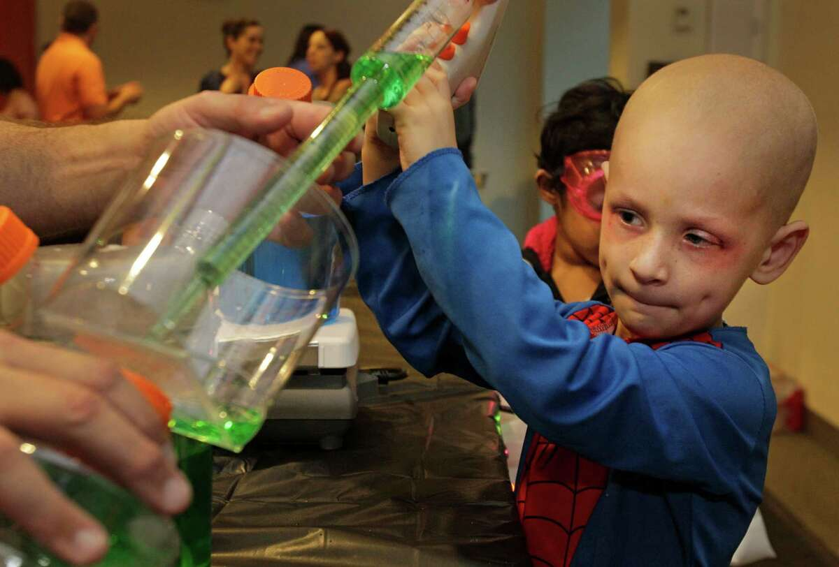 Micah Ahern, 4, of Arlington performs an experiment of liquid color transformation during the Mad Scientist Day at MD Anderson's Proton Therapy Center Wednesday, Oct. 30, 2013, in Houston. At the Halloween event organized by MD Anderson's Child Life Department, young patients and their siblings learned from doctors, nurses and other scientists by conducting experiments. Dressed in lab coats and other costumes, they conducted experiments involving filling rubber gloves with gas created by combining vinegar and baking soda, creating a substance called cloud goo with shaving cream and cornstarch, and other unique projects.