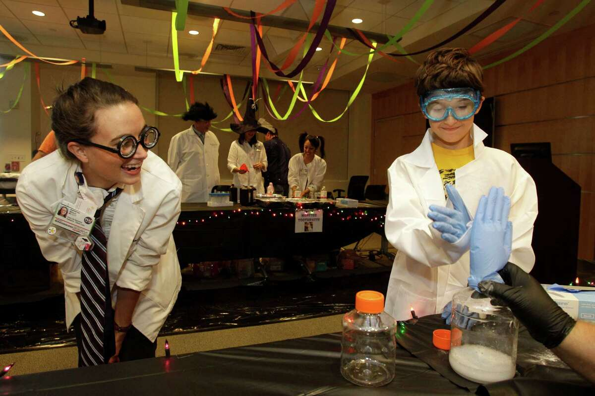 Kacie Wilson, left, a child life specialist, watches as Christo Anghel, 8, of San Diego, high fives the Invisible Hand during an experiment at the Mad Scientist Day at MD Anderson's Proton Therapy Center.