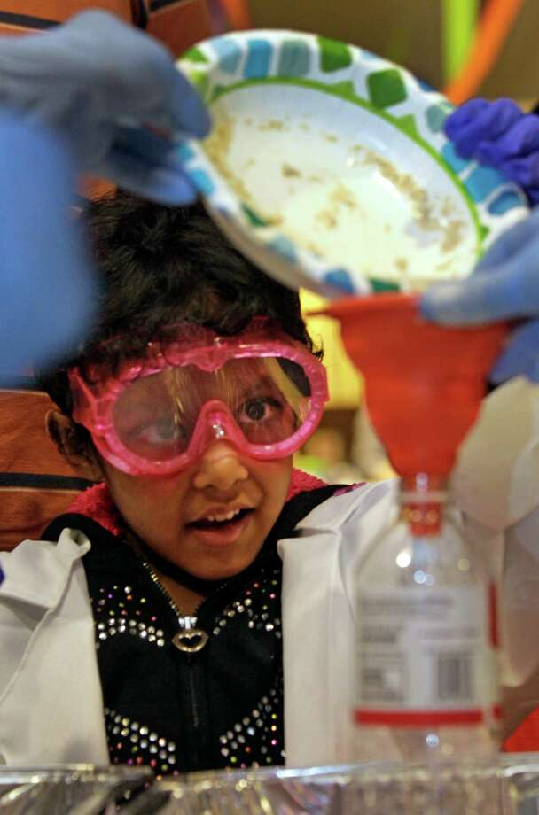 Naina Immaneni, 5, of Kingwood watches her monster toothpaste experiment during the Mad Scientist Day. Photo: Melissa Phillip, Houston Chronicle / © 2013  Houston Chronicle