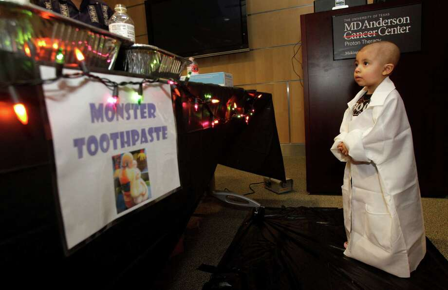 Jocelyn Diaz, 3, of San Antonio watches the monster toothpaste experiment that creates foams overflowing from a bottle during the Mad Scientist Day. Photo: Melissa Phillip, Houston Chronicle / © 2013  Houston Chronicle